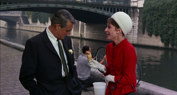 Grant and Hepburn stroll near Paris's Pont au Doubles in CHARADE